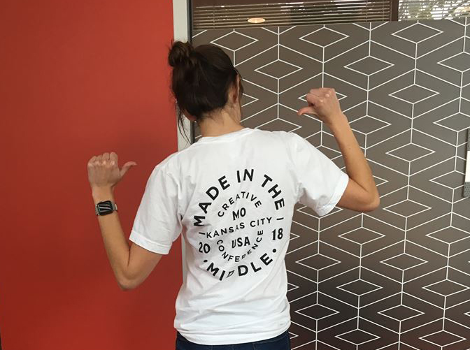 Woman facing away from camera wearing a Made in the Middle conference t-shirt