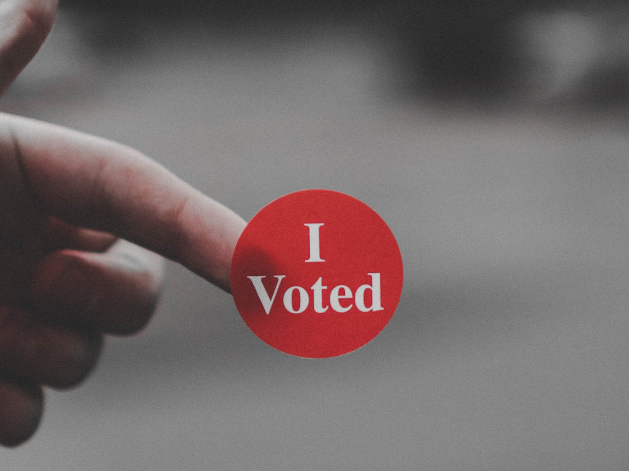 "Hand holding an ""I Voted"" sticker"
