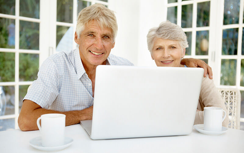 Photo of smiling older couple sitting at table with laptop