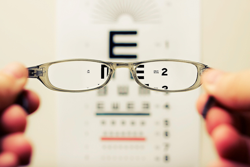 Photo of glasses in front of eye exam chart