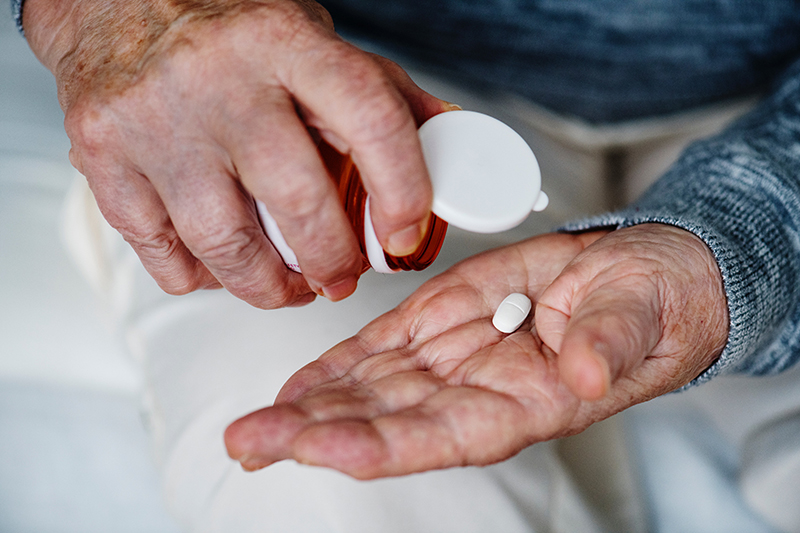 Hand of elderly person holding a pill