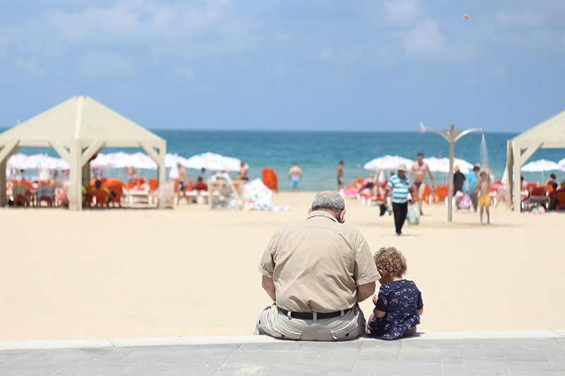 Photo of grandfather and grandchild by the beach