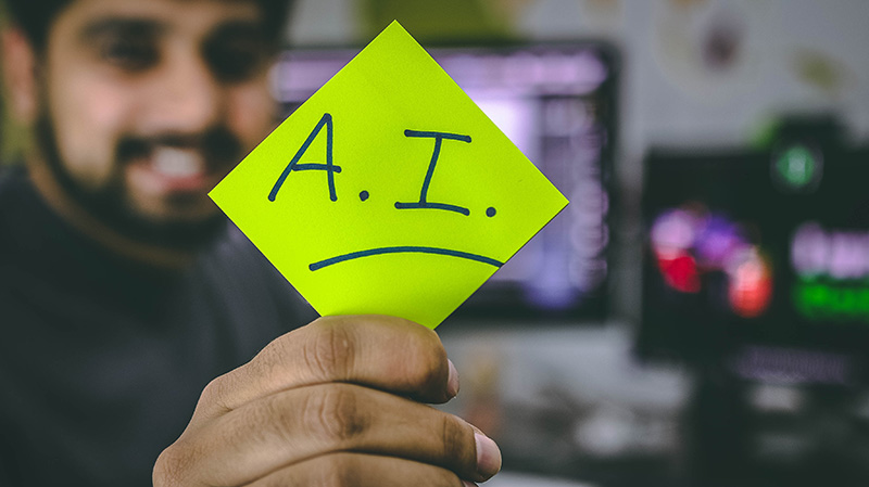 Man holding a post-it note that reads A.I.