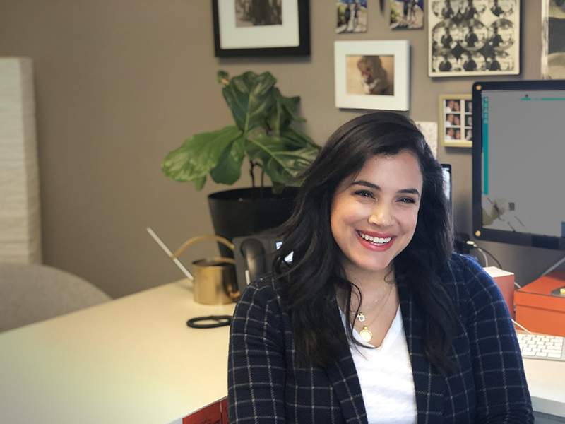 Photo showing a smiling woman with a desk behind her
