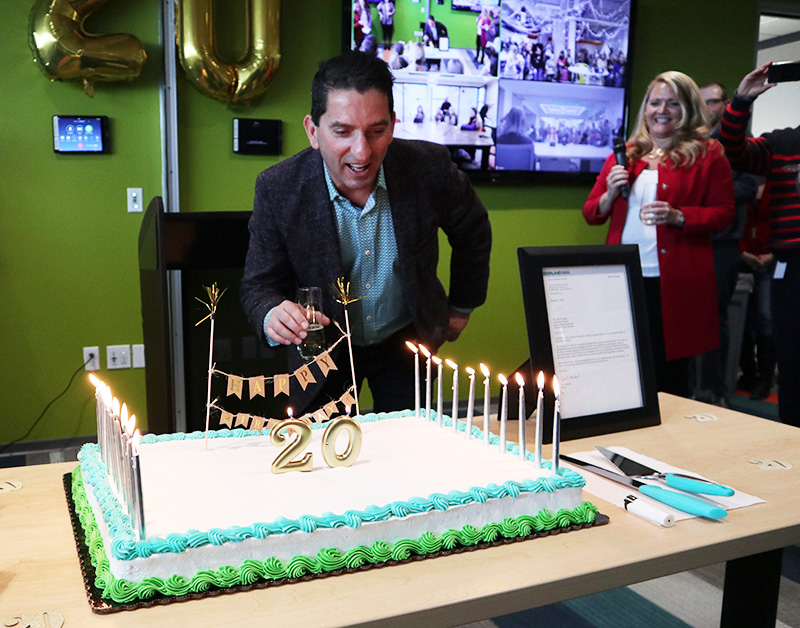 Photo of Intouch CEO Faruk Capan blowing out candles on a cake.
