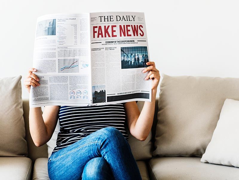 "Photo of woman holding newspaper with ""Fake News"" headline"