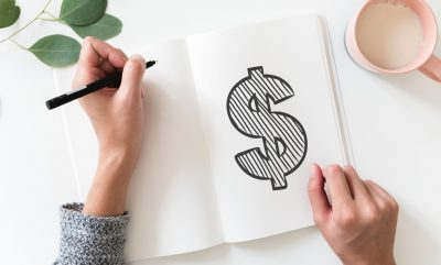 Image of woman's hand and notebook with drawn dollar symbol on white page