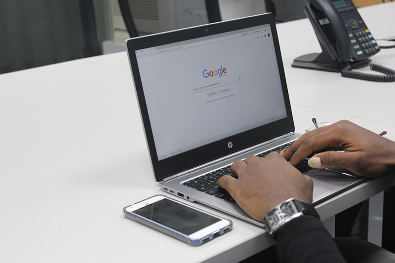 Man's hands typing on laptop with Google search bar on screen