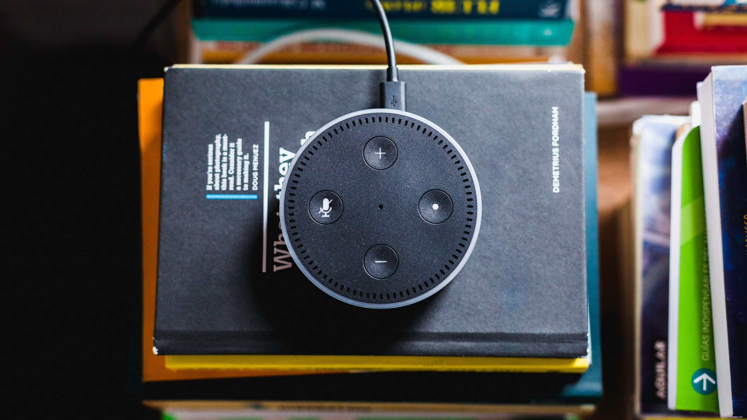 Amazon Echo Dot sitting on a stack of books