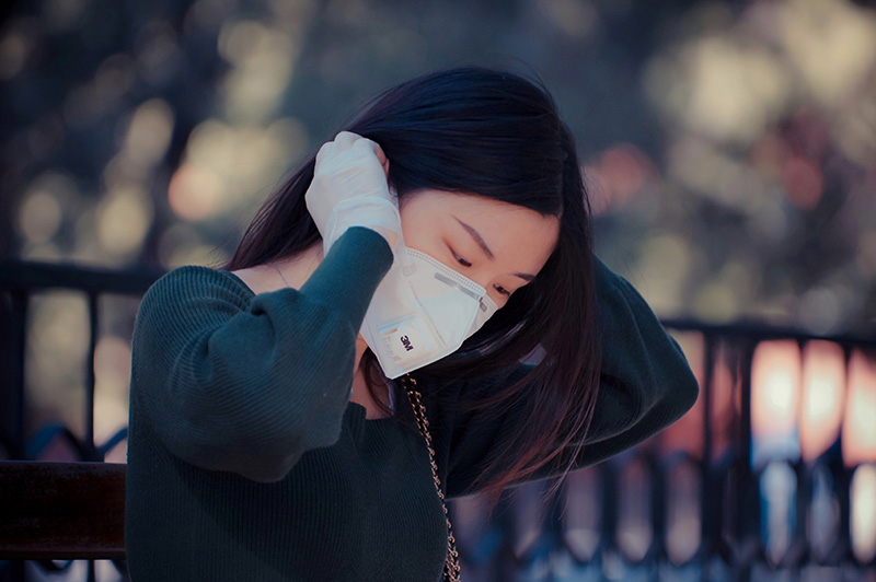 Young Asian woman securing her face mask