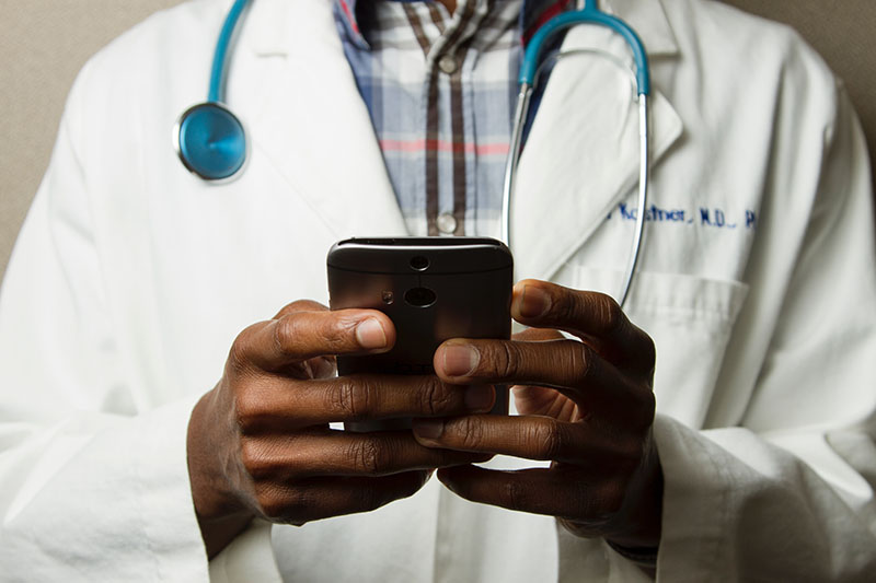 Black doctor with stethoscope and smart phone