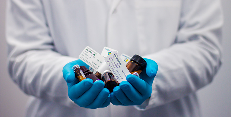 Image of medicine bottles held in hands wearing blue gloves