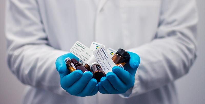 Image of medicine bottles held in hands wearing blue gloves