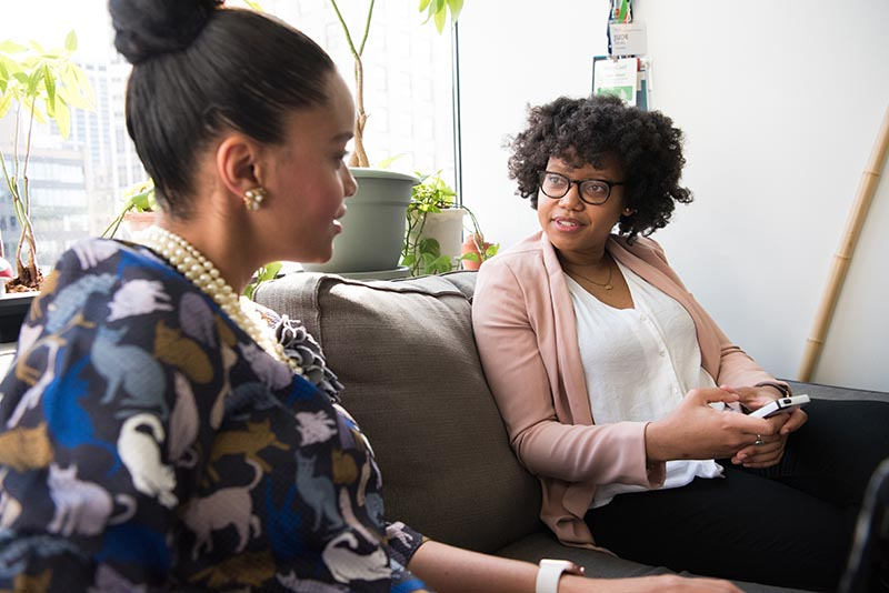 Image of two black women talking in office setting