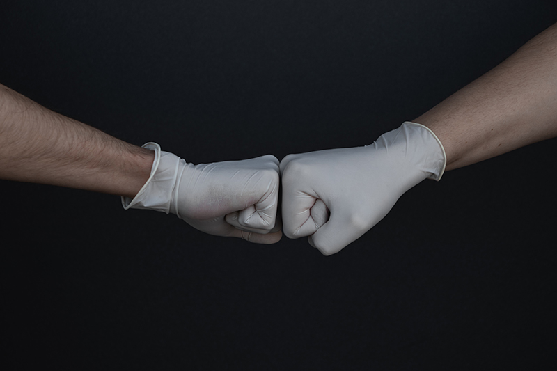 Image of two gloved hands doing a fist bump