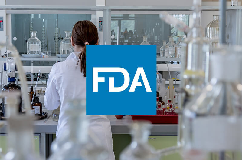 Woman in laboratory with FDA logo superimposed over the image