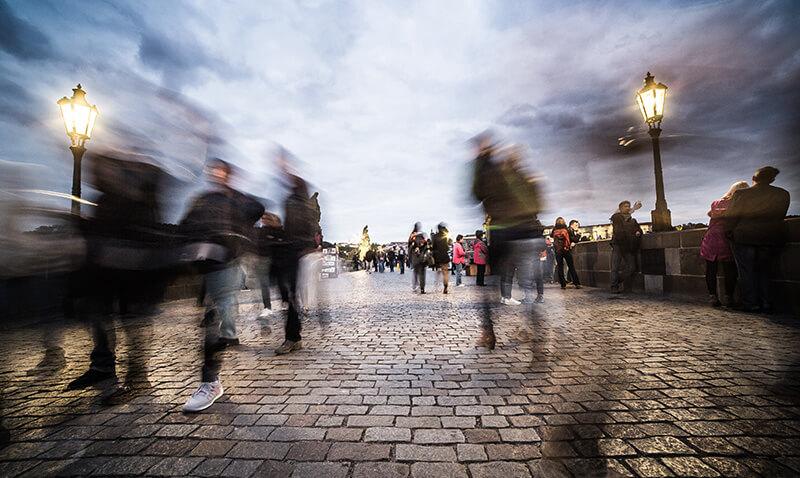 Blurry people walking on cobblestone street